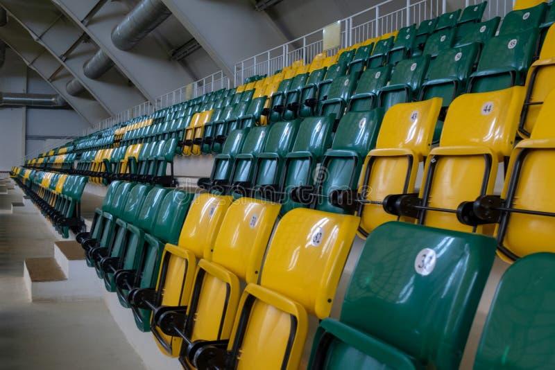 Het auditorium in de sporten complex met groene en gele plastic zetels E E royalty-vrije stock afbeelding