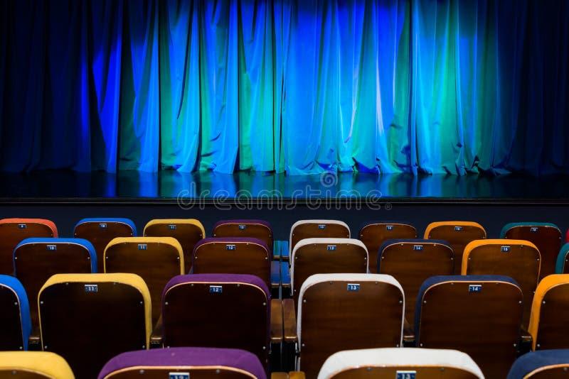 Het auditorium in het theater Blauwgroen gordijn op het stadium Multicolored toeschouwersstoelen De schijnwerper van de verlichti royalty-vrije stock afbeeldingen