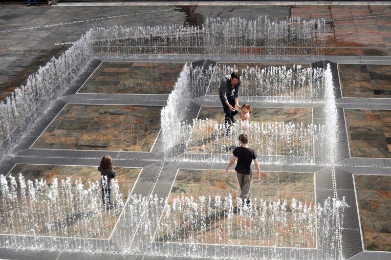 Het Australische mensenfamilie spelen in fontein bij Terras openlucht stock afbeeldingen
