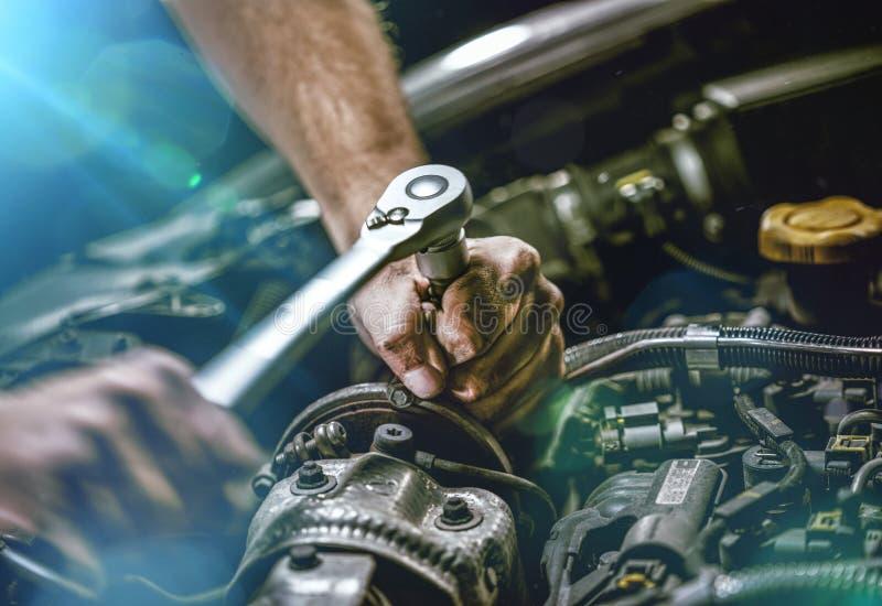 Het auto mechanische werken in garage De reparatiedienst stock afbeelding