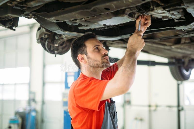 Het auto mechanische werken in garage De reparatiedienst stock fotografie