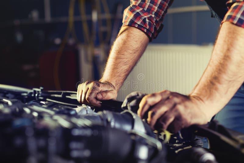 Het auto mechanische werken in garage De reparatiedienst royalty-vrije stock foto