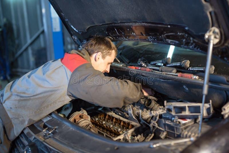 Het auto mechanische werken in garage De reparatiedienst stock afbeeldingen