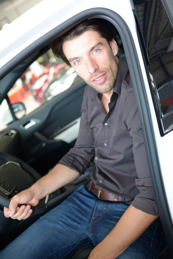 Het autohandel drijven - de jonge knappe mens zit in een auto en het kopen a stock afbeeldingen