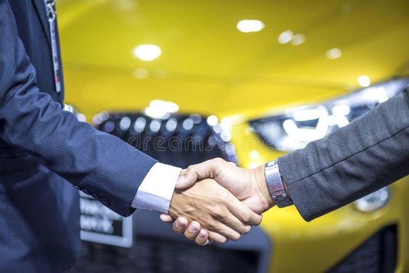 Het autohandel drijven; Twee zakenlieden schudden handen met nieuwe autoachtergrond stock afbeelding
