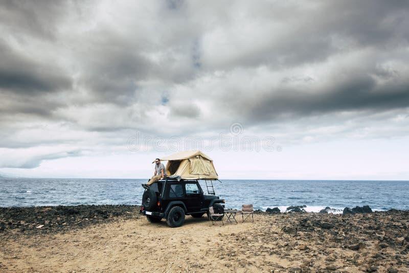 Het avonturenconcept voor de Kaukasische mens gaat zitten en rust op het dak van zijn auto met tent - de levensstijl van de reizi stock foto