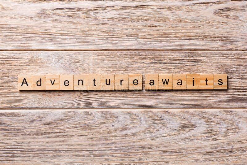 Het avontuur wacht op woord dat op houtsnede wordt geschreven Het avontuur wacht op tekst op houten lijst voor uw het desing, con stock afbeelding