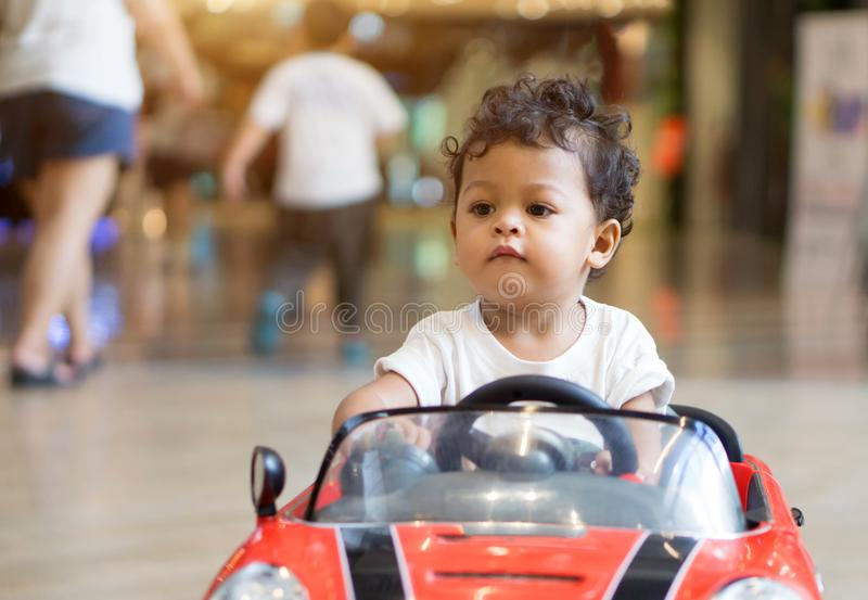 Het Aziatische babyjongen drijven in een rood autostuk speelgoed stock fotografie