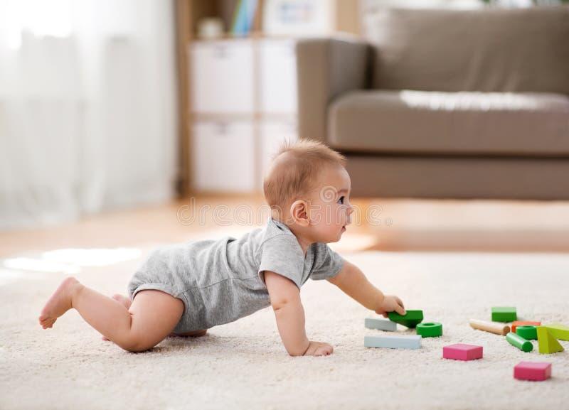 Het Aziatische babyjongen spelen met stuk speelgoed blokken thuis stock fotografie