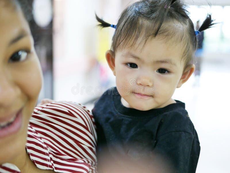 Het Aziatische babymeisje geniet van nemend foto, bekijkend de vlek waar haar moeder die en haar richten begeleiden om te bekijke stock afbeeldingen