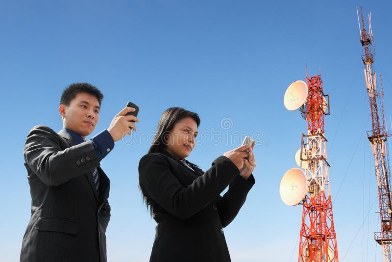 Het Aziatische bedrijfsmensen texting en antenne stock afbeelding