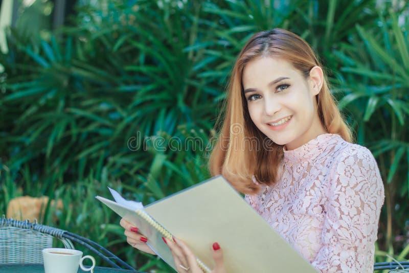 Het Aziatische bedrijfsvrouwen glimlachen werkend en schrijvend een boek en che royalty-vrije stock foto's