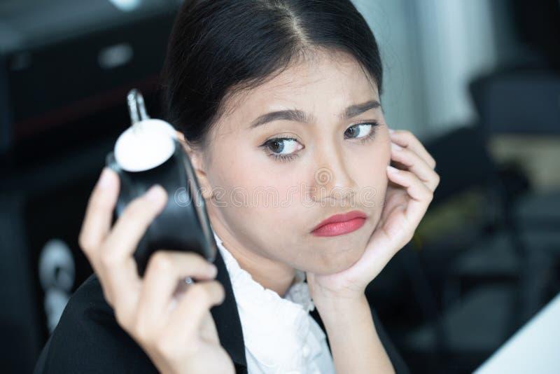Het Aziatische bedrijfsvrouwengevoel vermoeide en bored het wachten op iemand die laat op het werk komen stock fotografie