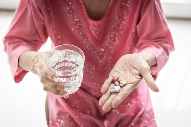 Het Aziatische bejaarde neemt en eet geneesmiddelen en vitaminen royalty-vrije stock foto