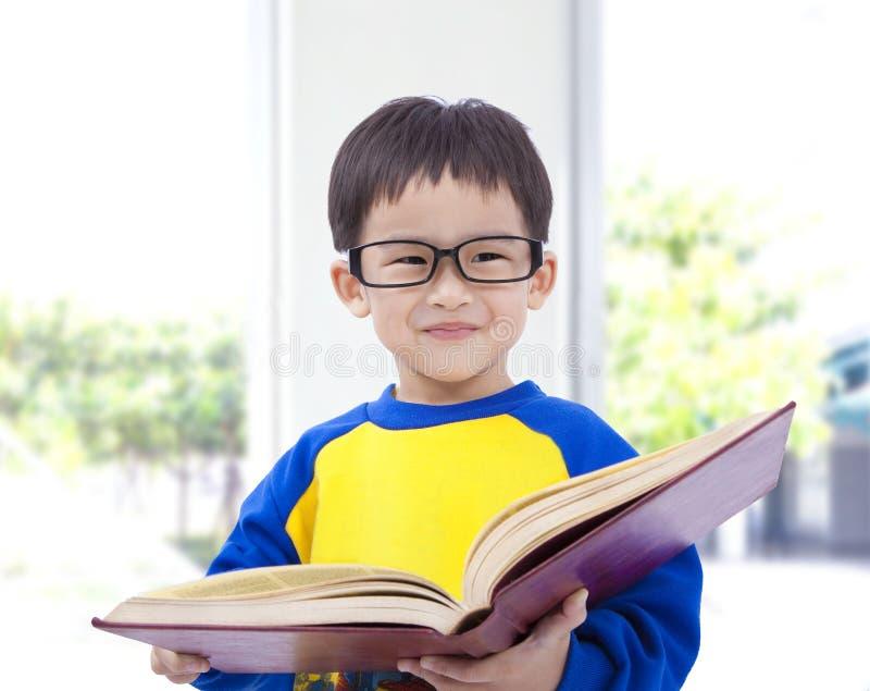 Het Aziatische boek van de jong geitjeholding royalty-vrije stock foto's