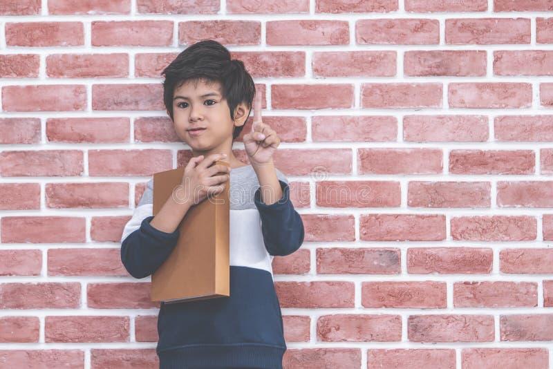 Het Aziatische boek van de jongensholding op bakstenen muurachtergrond stock foto's