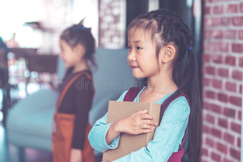Het Aziatische boek van de meisjesholding op bakstenen muurachtergrond royalty-vrije stock foto's