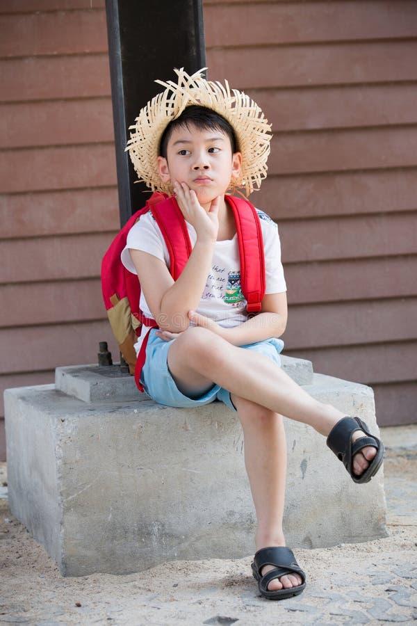 Het Aziatische bored rode kind denkt terwijl stock foto