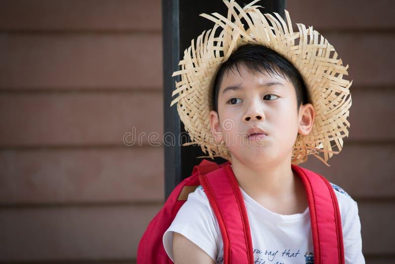 Het Aziatische bored rode kind denkt terwijl stock foto's