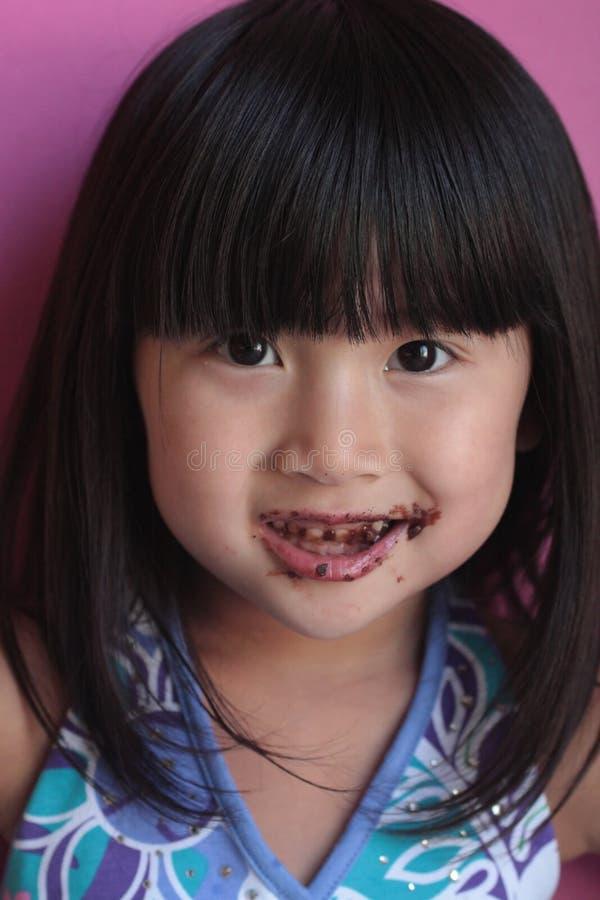 Het Aziatische Chinese slordige gezicht van de Chocolade van het Meisje   royalty-vrije stock afbeeldingen