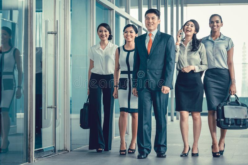 Het Aziatische commerciële team van stafmedewerkers die in bureau lopen schrikt zeer af stock foto