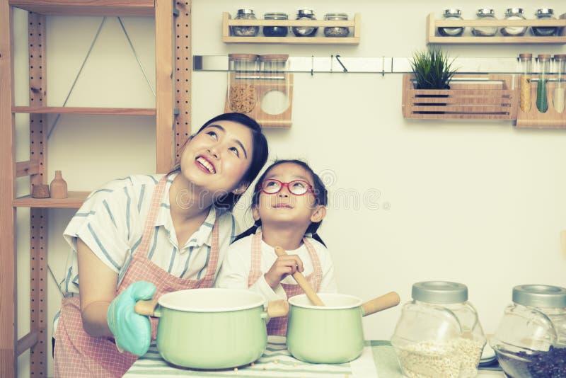 Het Aziatische de vrouwenmamma en dochter in keuken zowel kijken omhoog met gelukkig als glimlachen gezicht, proces in uitstekend royalty-vrije stock foto