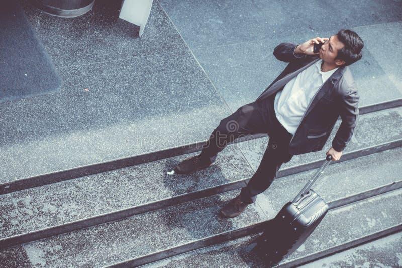 Het Aziatische elegante kostuum die van de zakenmanslijtage mobiele telefoon spreken terwijl het lopen van holdingskoffer openluc stock foto's