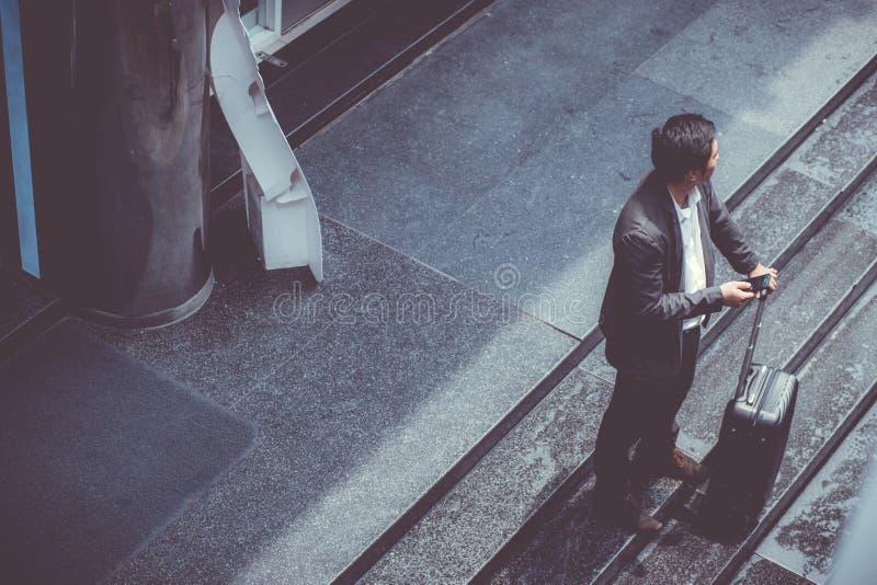 Het Aziatische elegante kostuum die van de zakenmanslijtage mobiele telefoon spreken terwijl het lopen van holdingskoffer openluc royalty-vrije stock fotografie