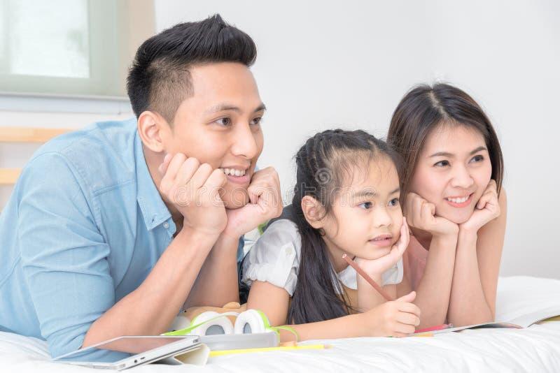 Het Aziatische familie gelukkige glimlachen en ontspant thuis op bed royalty-vrije stock fotografie