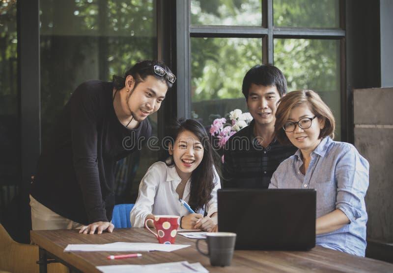 Het Aziatische freelance teamwerk die aan computer voor project kijken succes stock foto's