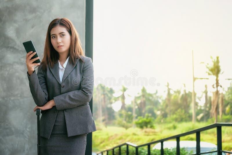 Het Aziatische gebruik van vrouwenzakenlieden smartphones om het werk en busi te contacteren royalty-vrije stock foto