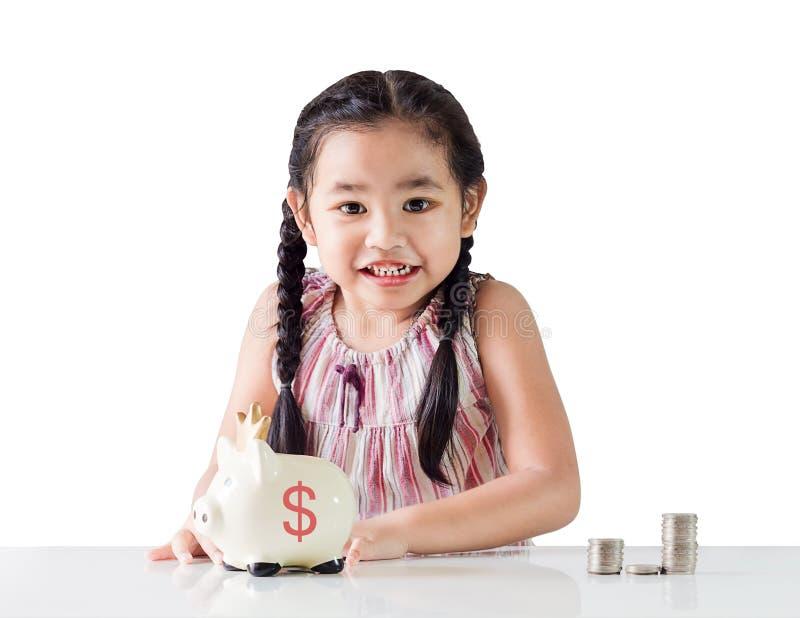 Het Aziatische geld van de meisjebesparing in een spaarvarken Geïsoleerdj op witte achtergrond royalty-vrije stock afbeeldingen