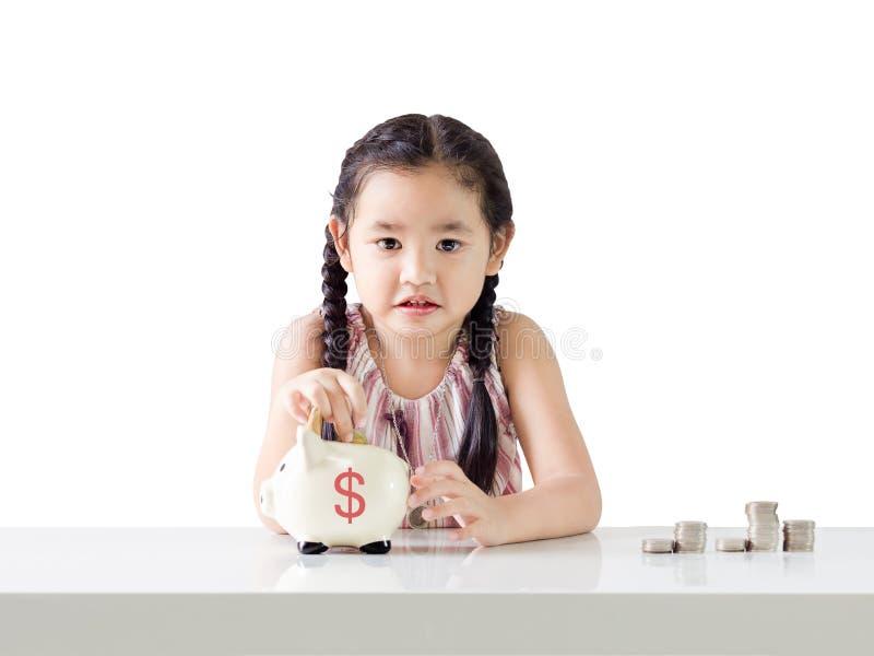Het Aziatische geld van de meisjebesparing in een spaarvarken Geïsoleerdj op witte achtergrond royalty-vrije stock foto's