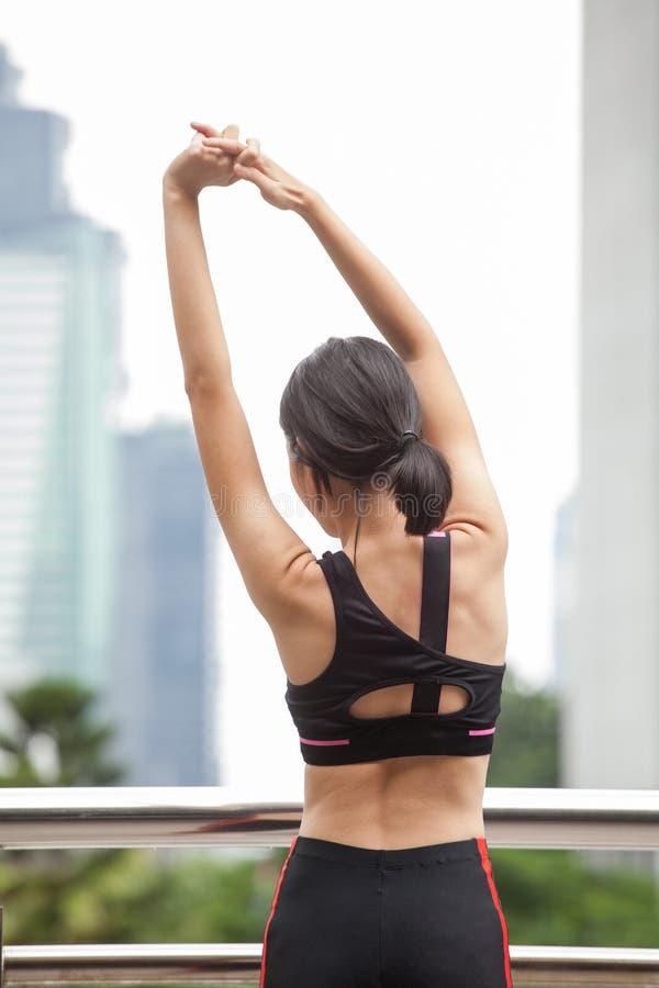 het Aziatische geschiktheids jonge vrouw uitrekken zich op een training die van de spoorbrug op straat in stedelijke stad uitoefe royalty-vrije stock foto's