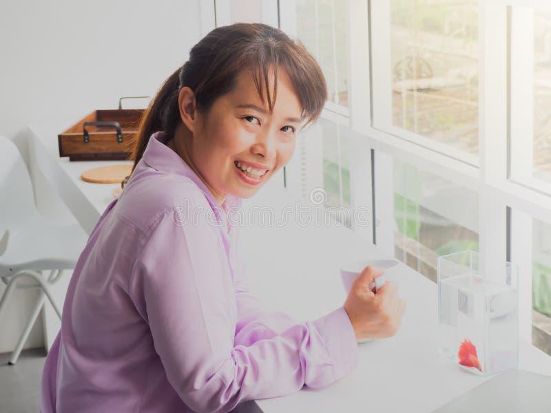 Het Aziatische glas van de bedrijfsvrouwenholding koffie in Koffie met vissen s stock afbeelding