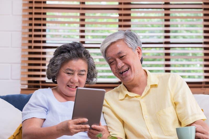 Het Aziatische hogere paar leert aan het gebruiken van lijst gegevens verwerkt thuis op bank in woonkamer oudste met technologie  royalty-vrije stock foto