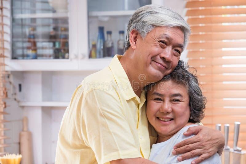 Het Aziatische hogere paar omhelst togerther en bekijkend camera en thuis glimlachend in keuken r royalty-vrije stock afbeelding