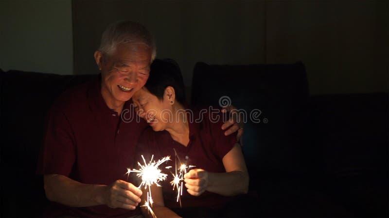 Het Aziatische hogere paar vieren samen fonkelt thuis vuurwerk s royalty-vrije stock afbeelding