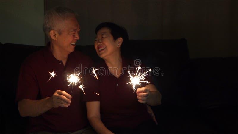 Het Aziatische hogere paar vieren samen fonkelt thuis vuurwerk s royalty-vrije stock foto