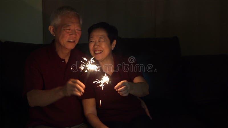 Het Aziatische hogere paar vieren samen fonkelt thuis vuurwerk s stock afbeelding