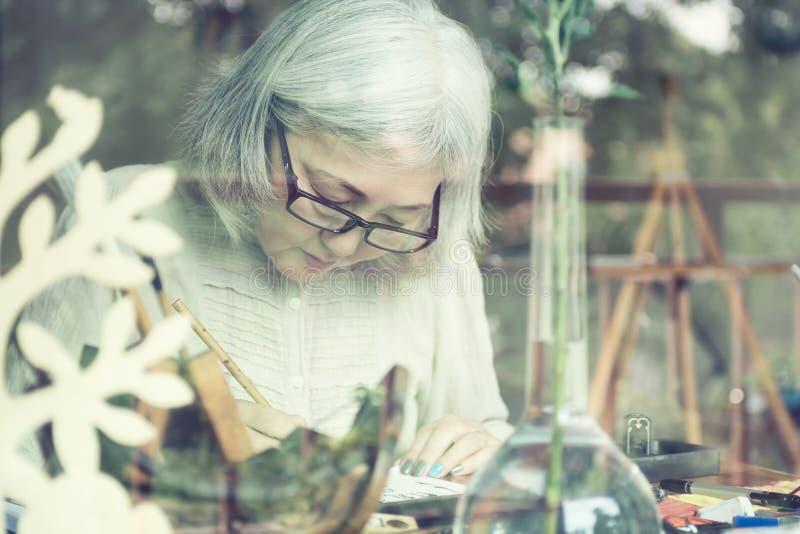 Het Aziatische hogere vrouw schilderen bij haar huisstudio royalty-vrije stock afbeelding