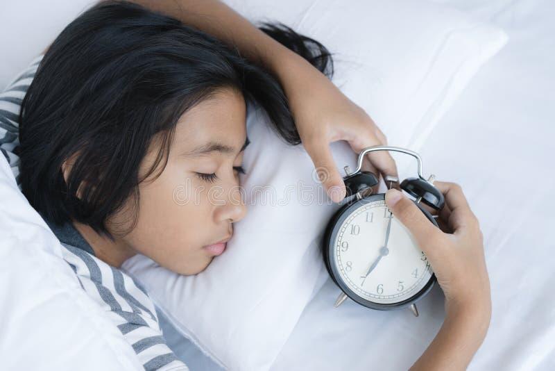 het het Aziatische hoofdkussen en bed van de meisjeslaap bij slaapkamer in huis Het leuke meisje ontspant slaap op het bed stock foto