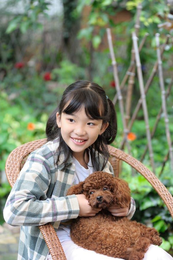 Het Aziatische jong geitje spelen met hond royalty-vrije stock afbeeldingen