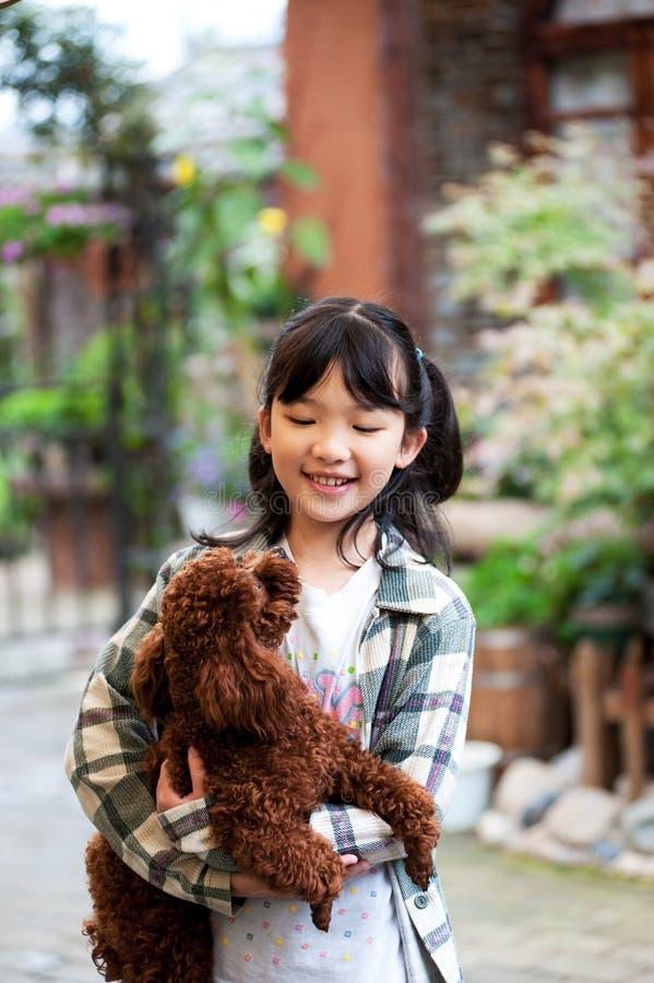 Het Aziatische jong geitje spelen met hond stock foto's