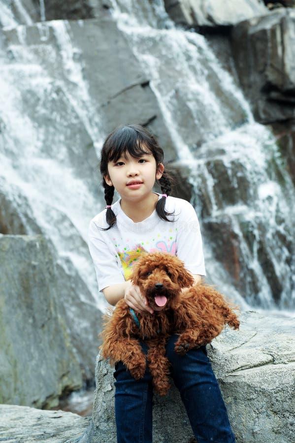 Het Aziatische jong geitje spelen met poedelhond royalty-vrije stock afbeeldingen