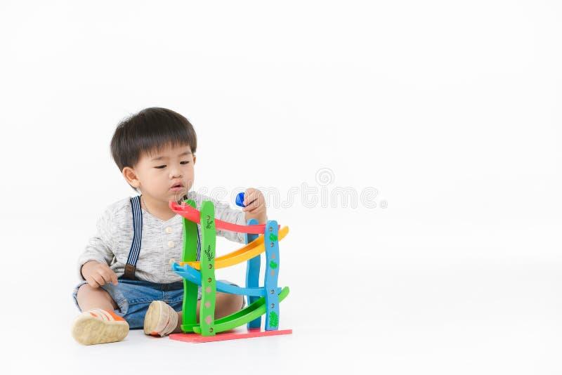 Het Aziatische jong geitje spelen met stuk speelgoed stock foto's