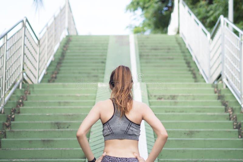 Het Aziatische jonge het lichaam van de vrouwenopwarming uitrekken zich vóór ochtendoefening en het aanstoten onder warme lichte  stock foto
