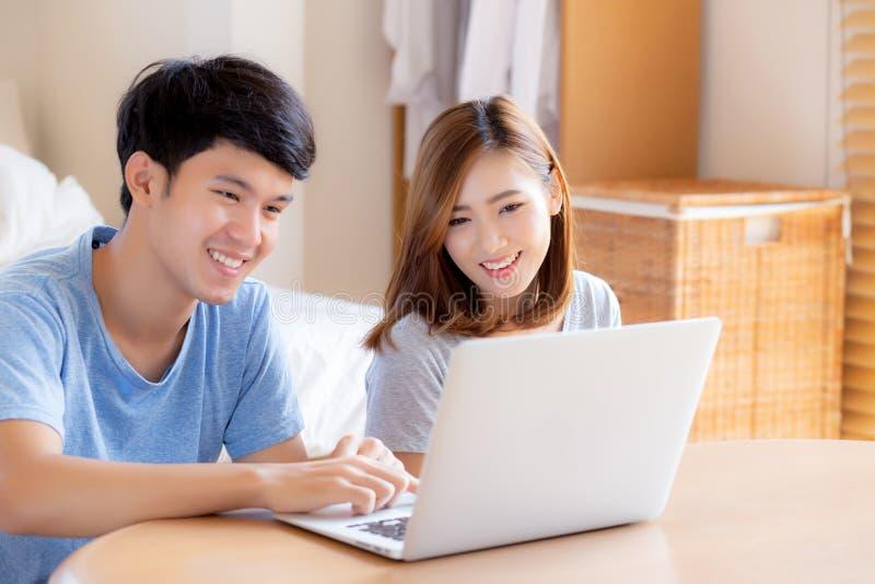 Het Aziatische jonge paar die laptop computer met behulp van denkt en Internet samen, man en vrouwen het toevallige het glimlache royalty-vrije stock foto's