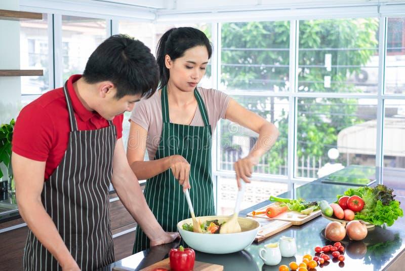 Het Aziatische jonge paar in schort, maakt samen het koken De slasaus van de vrouwenmengeling met groente in grote kom royalty-vrije stock foto's
