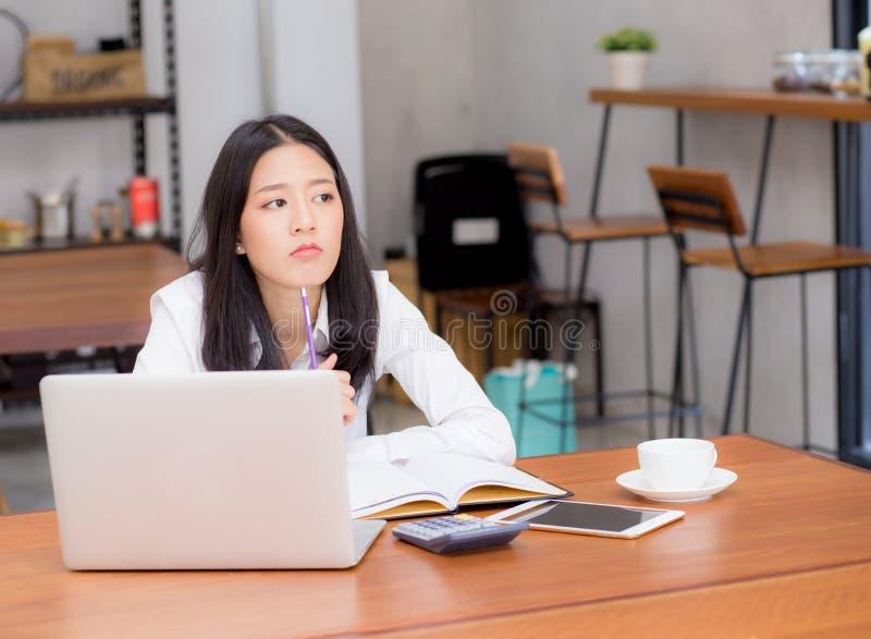 Het Aziatische jonge vrouw werken online met laptop en denkt project voor idee stock afbeeldingen